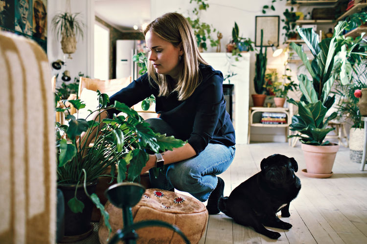 Woman with dog in potted plants