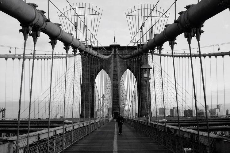 Man walking on brooklyn bridge against sky