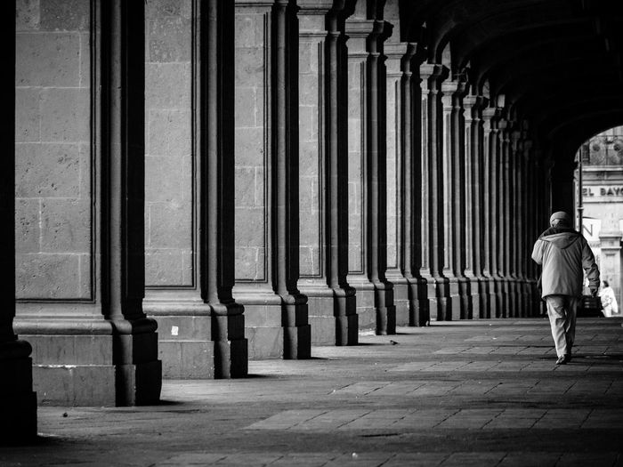 Rear view of man walking by columns