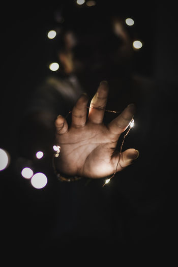 Person hand holding illuminated lights at night
