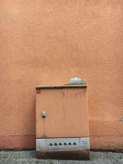 Abandoned mailbox on street by wall