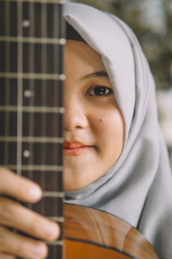 Portrait Of Girl Wearing Hijab Holding Guitar