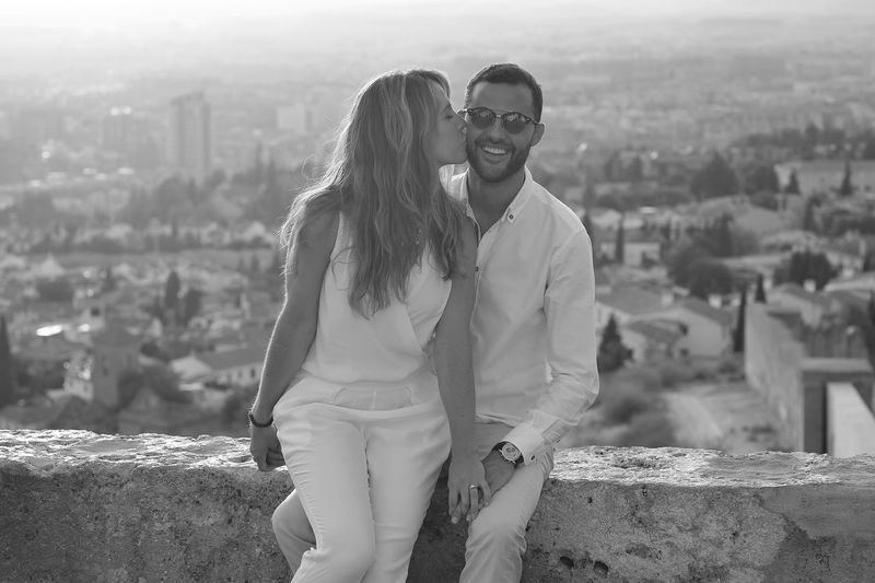 Young Woman Kissing Man While Sitting On Retaining Wall Against Cityscape