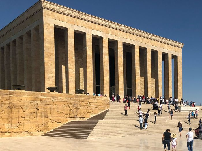 Tourists visiting an?tkabir against clear blue sky during sunny day