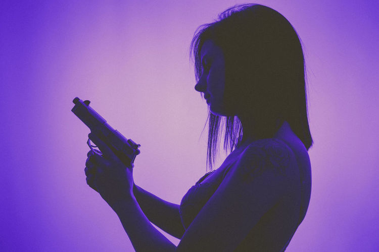 Side view of young woman holding handgun against purple background