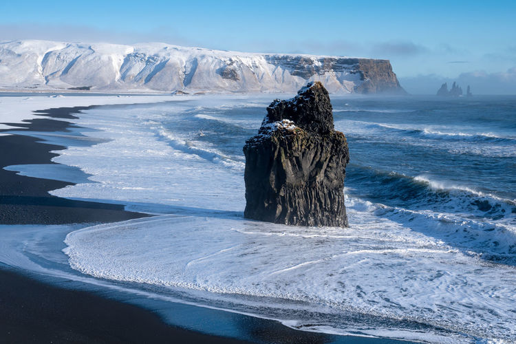 Statue of frozen sea against sky during winter
