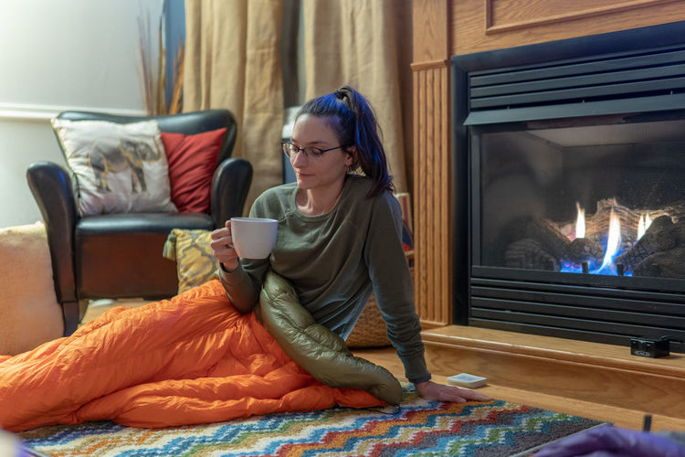 Woman sitting on bed at home