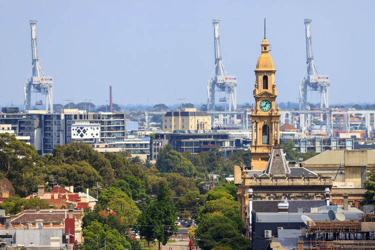 South Melbourne's city hall clock tower, with shipping cranes in the background Cityscape Architecture Building Exterior Built Structure City Cityscape Clear Sky Clock Tower Crane - Construction Machinery Day Nature No People Outdoors Place Of Worship Religion Sky Spirituality Tower Travel Destinations Tree Urban Skyline