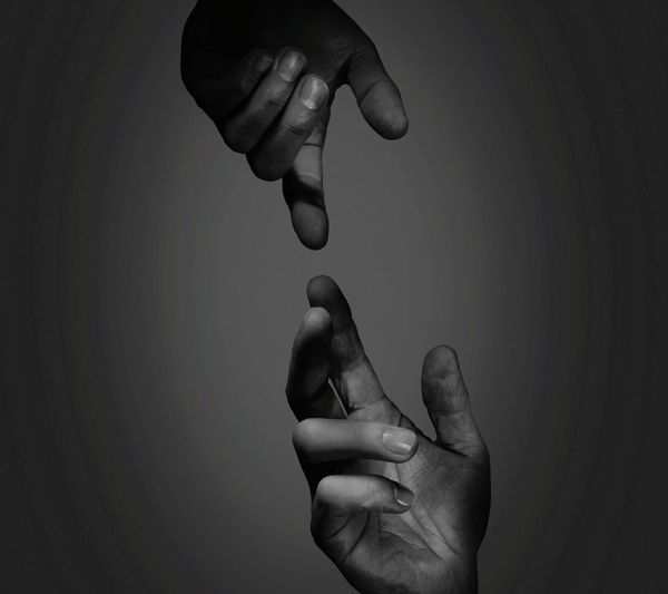Cropped hands of people against gray background