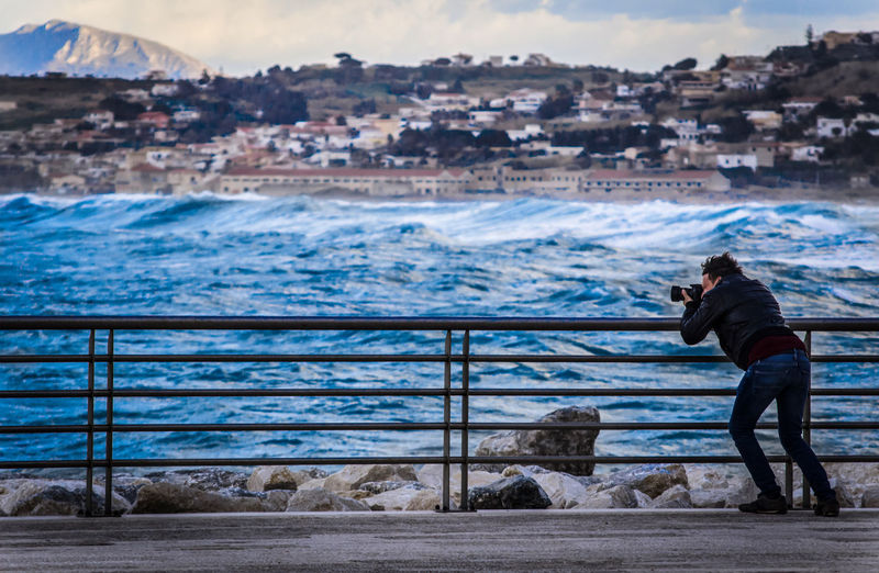 Man photographing while standing on railing by sea against sky