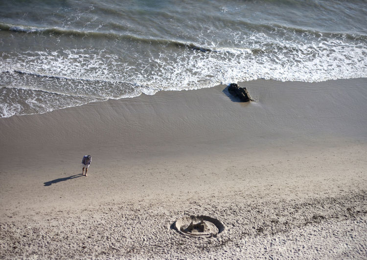High angle view of man walking on shore with sandcastle at beach