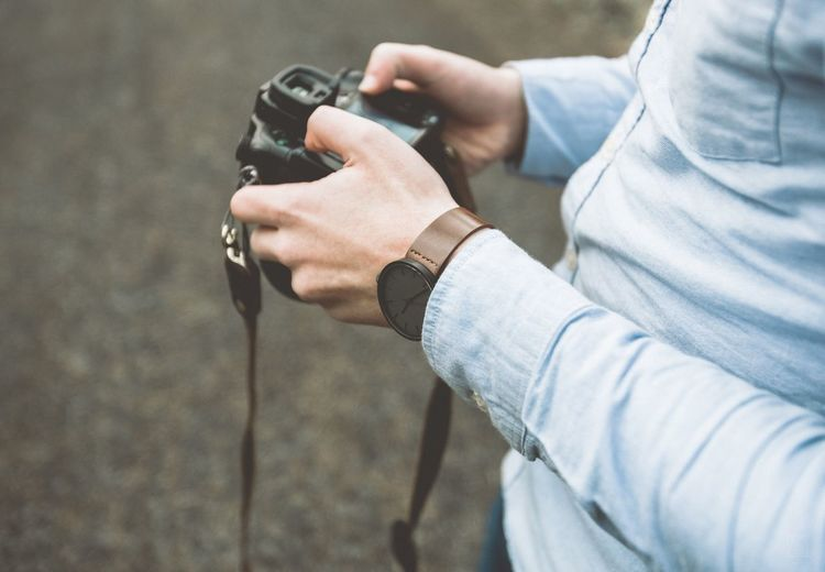 Close-Up Of Man With Camera In Hands