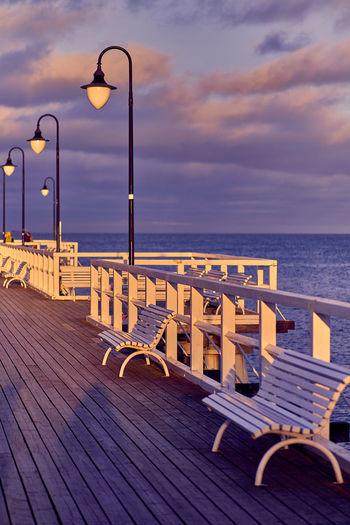 Chairs on pier against sky during sunset