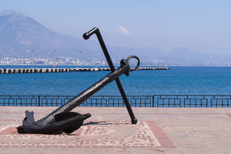 Statue of anchor by river with jetty