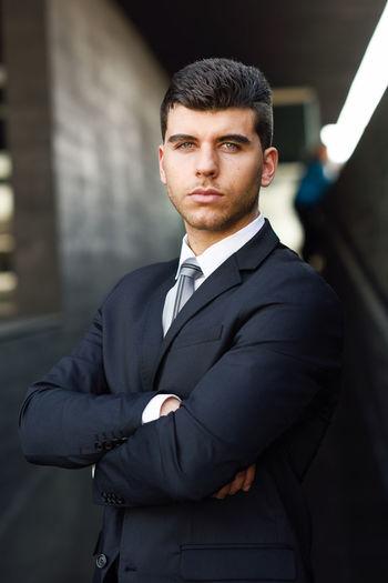 Portrait of handsome young businessman standing in corridor