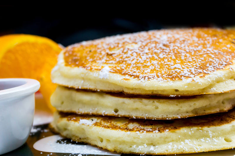 Close-up of pancakes garnished with powdered sugar on table