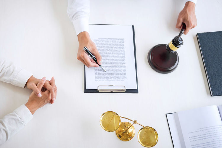 Cropped Hands Of Lawyer With Client At Desk In Office