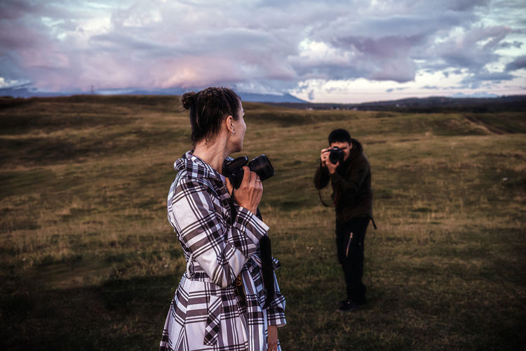 Friends standing on land against sky