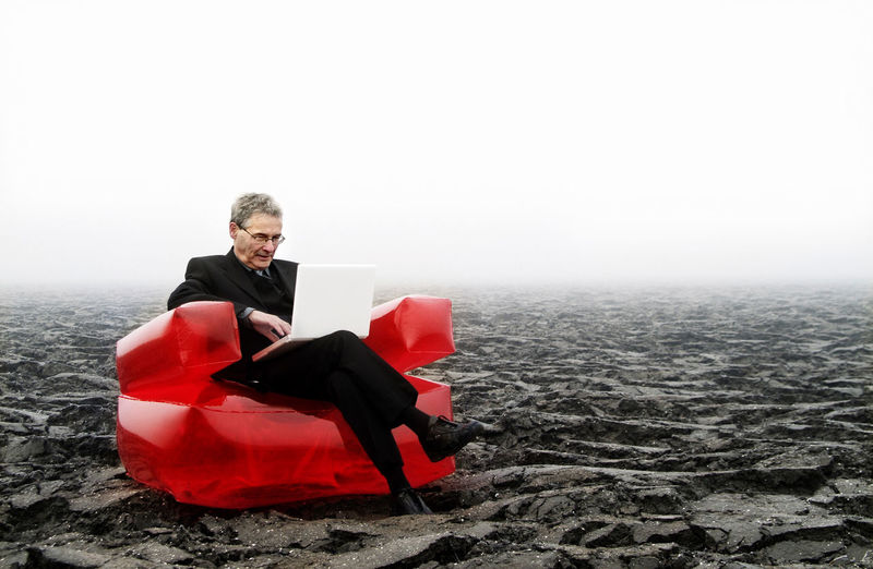 Businessman using laptop while sitting on landscape against sky