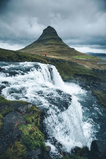 Scenic view of waterfall by mountain against sky