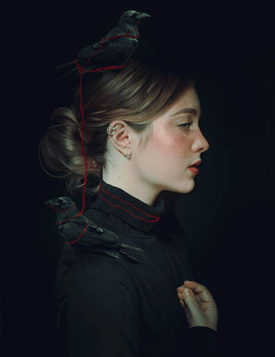 Side view of woman with bird against black background
