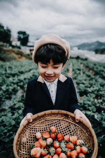 Full length of boy holding ice cream in basket