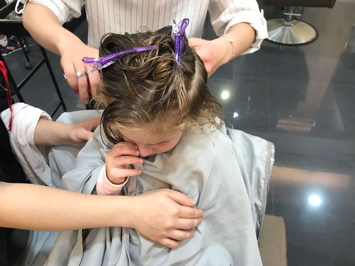 Hairdressers cutting girl hair in shop