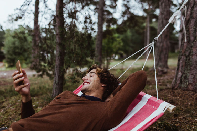 Young man sitting on hammock in forest