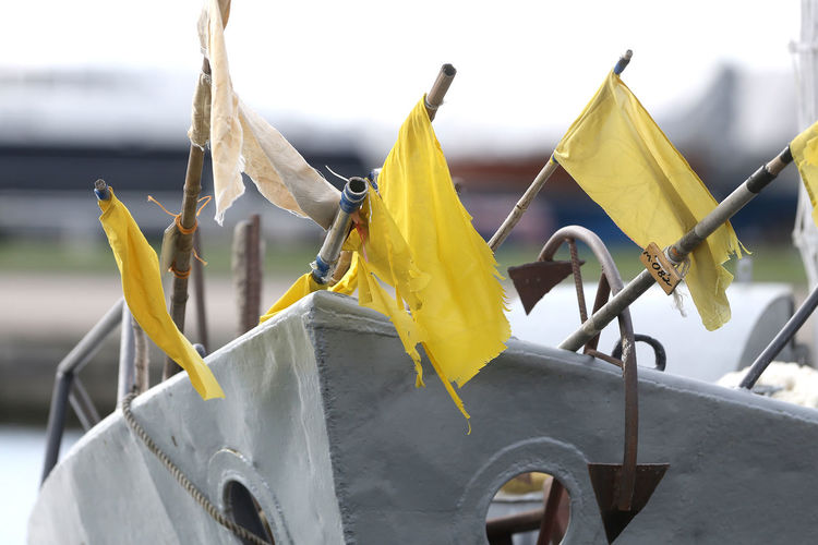 Close-up of yellow flags against sky