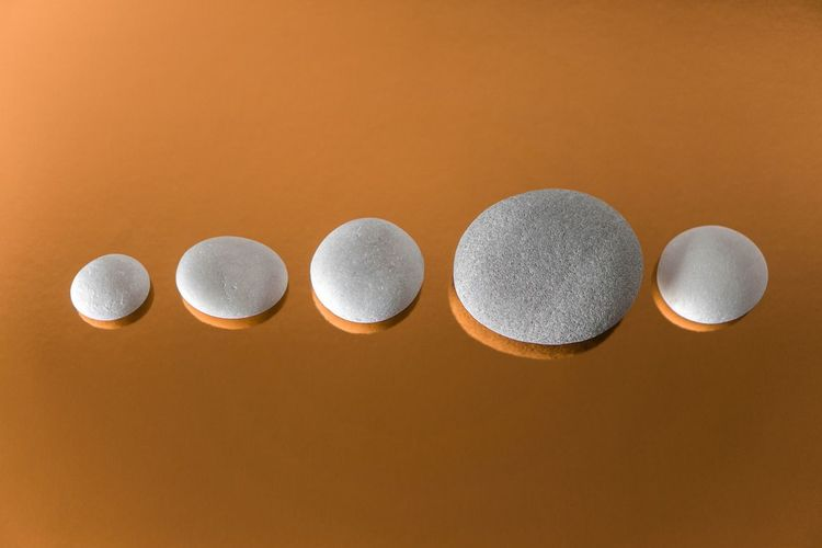 High angle view of pebbles arranged over orange background