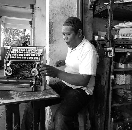 Man repairing typewriter