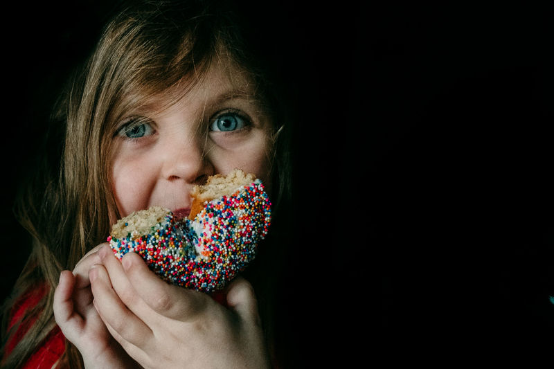 Portrait Headshot One Person Black Background Food And Drink Food Looking At Camera Close-up Hands Covering Mouth Sweet Food Eating Child Donut Sprinkles