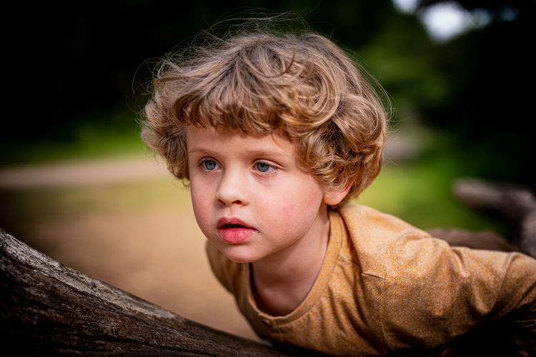 Beautiful boy playing on a trunk in epping forest