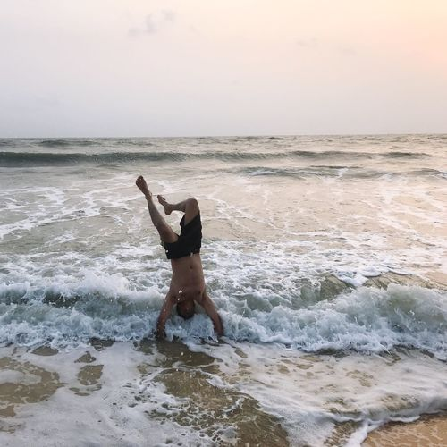 Waves splashing on man practicing handstand on shore against during sunset