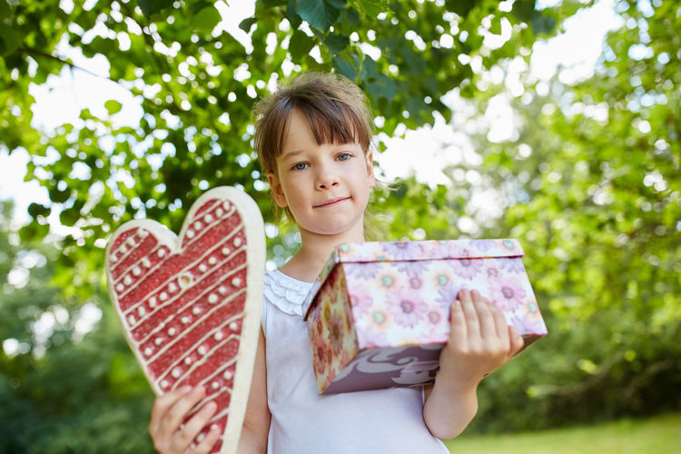 Portrait of girl holding heart shape and gift box against trees