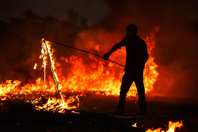 Silhouette Man Holding Burning Rope With Stick At Field
