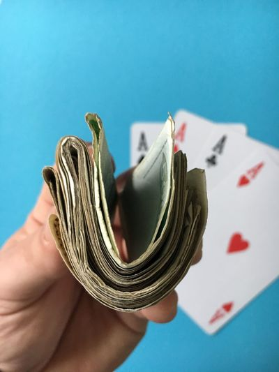 Cropped image of hand holding paper currency with aces cards at casino table