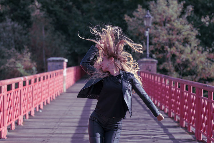 Adult Architecture Bridge Built Structure Casual Clothing Footbridge Front View Hair Hair Toss Hairstyle Human Arm Leisure Activity Lifestyles Long Hair Motion One Person Outdoors Railing Real People Three Quarter Length Tousled Hair Women Young Adult
