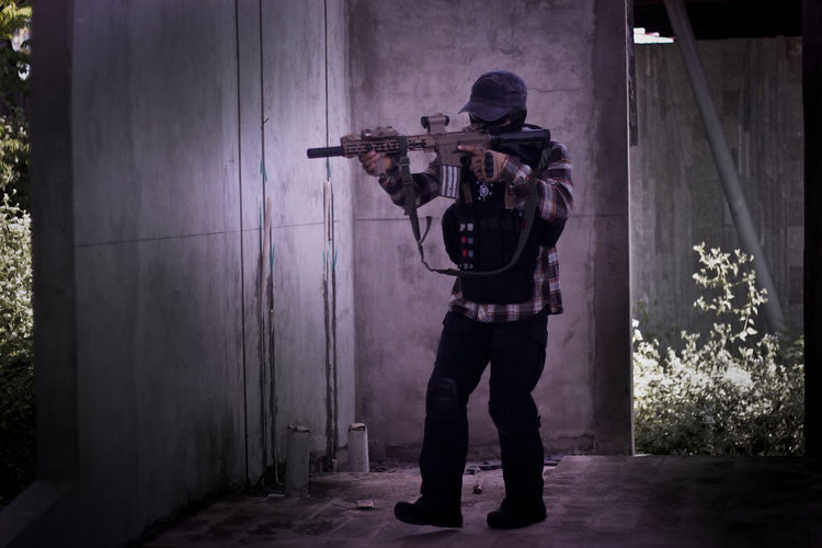 Full length of man holding rifle standing by wall outdoors
