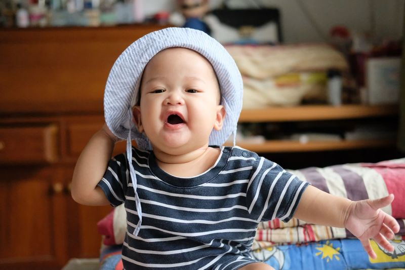 Portrait Of Cute Baby Boy In Hat At Home
