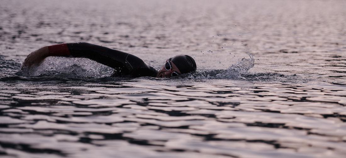 Man swimming lake during sunset