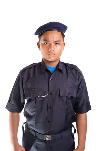 Young Asian man in police uniform isolated on white background. White Background Studio Shot Cut Out One Person Clothing Looking At Camera Standing Young Adult Cap Portrait Men Police Officer Security Face Smile Service Uniform Occupation Young Men Front View Indoors  Hat Three Quarter Length Teenager