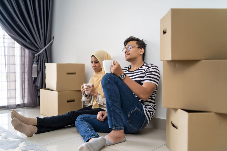 asian couple moving out and moving in into new house Adult Beginnings Box Box - Container Cardboard Cardboard Box Casual Clothing Front View Full Length Home Ownership Indoors  Lifestyles Men Moving House Packing Positive Emotion Real People Sitting Togetherness Two People Women Young Adult Young Women