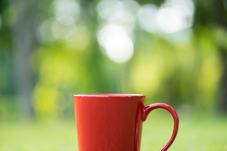 Close-Up Of Red Coffee Cup On Field
