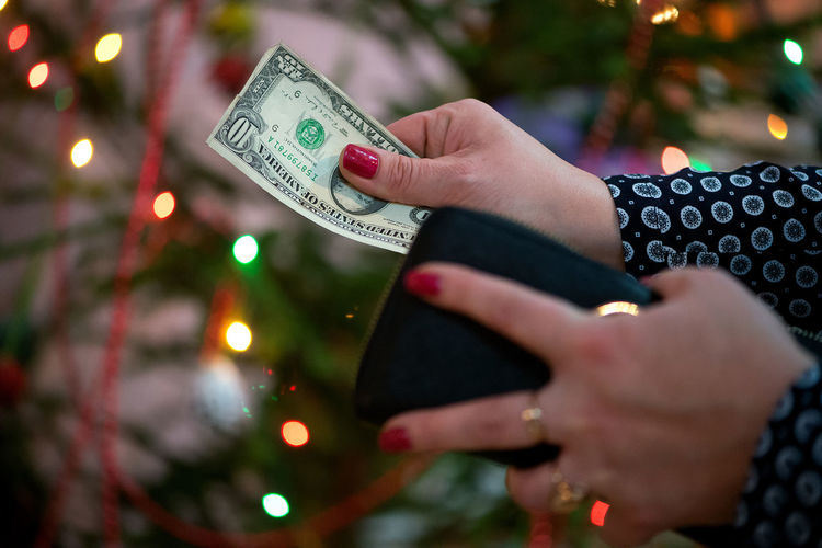 Cropped hands of woman holding paper currency against christmas tree