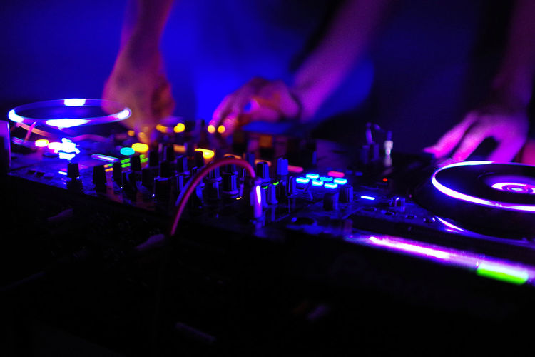 Cropped Image Of People Playing Illuminated Dj In Club