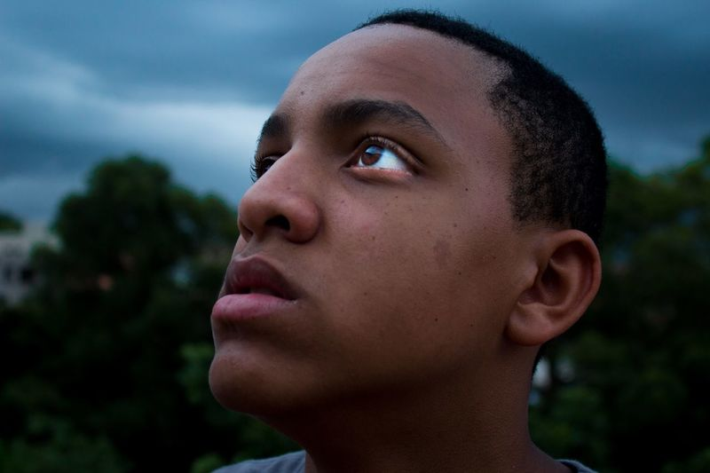 Close-Up Of Teenage Boy Looking Up Against Cloudy Sky