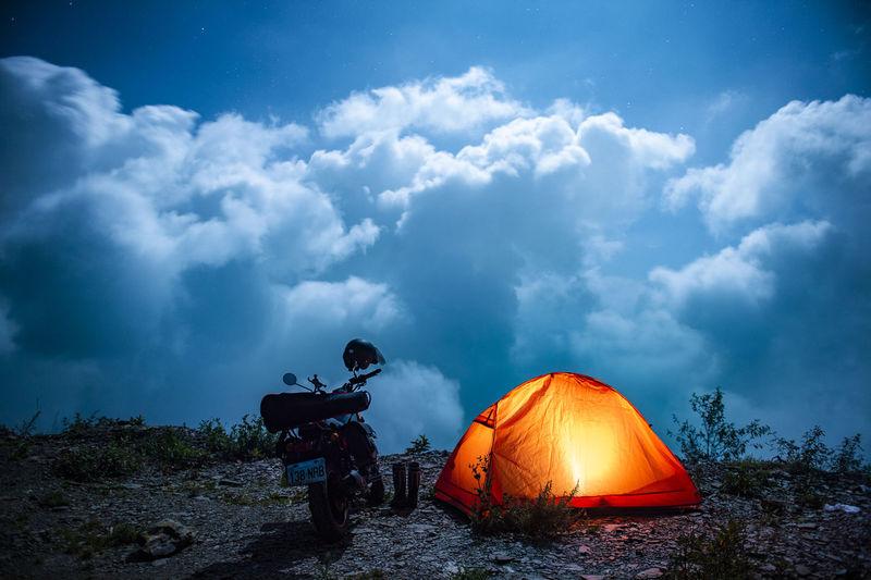 Rear view of men in tent on field against sky