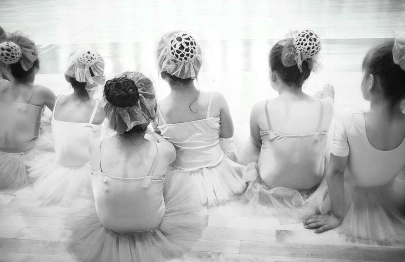 Rear View Of Ballet Dancer Girls Sitting On Floor
