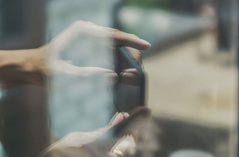 Cropped image of hand holding mobile phone seen through glass window